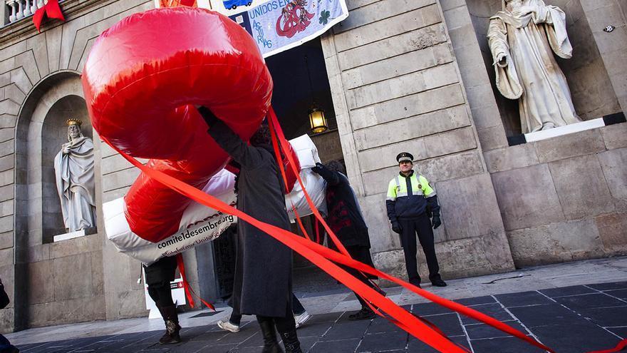 Una voluntaria traslada el lazo rojo que simboliza la lucha contra el sida, este mediodía, en la plaza Sant Jaume de Barcelona. (Carmen Secanella)