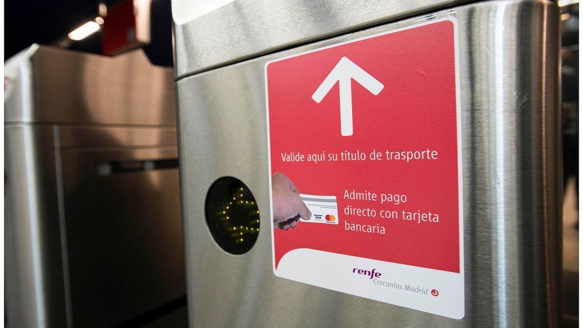 Entrada a uno de los tornos de Cercanía, con una pegatina que avisa de la validación con tarjeta bancaria