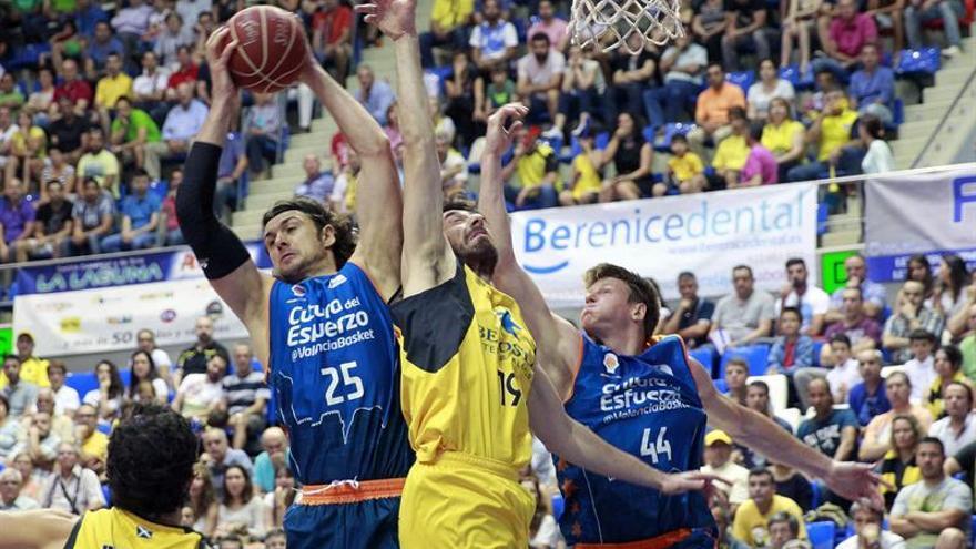 Los pívots del Valencia Basket Kresimir Loncar (i) y Luke Harangody (d) luchan por el balón con el pívot griego del Iberostar Tenerife Fotios Lampropoulos