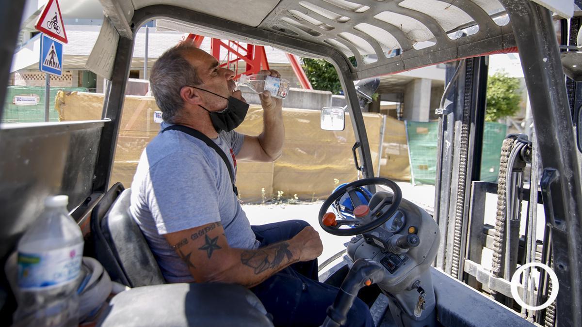Un trabajador se refresca en una jornada de intenso calor en junio en Córdoba