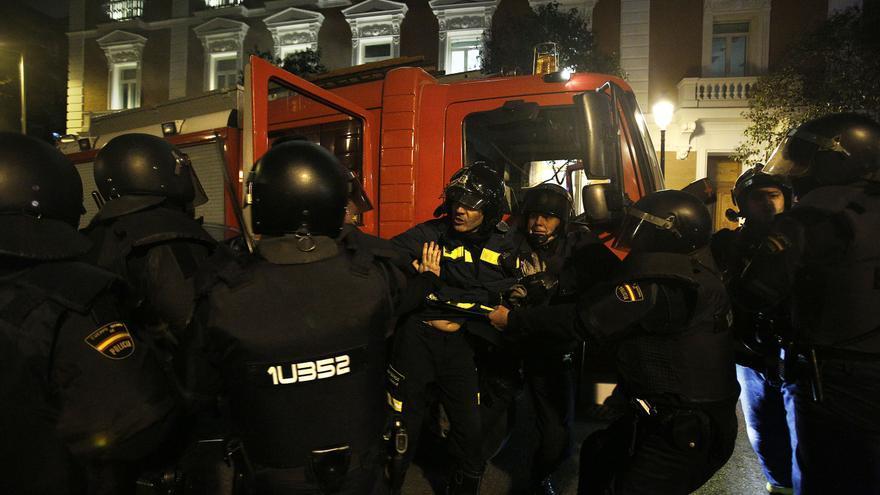 Varios agentes se dirigen a uno de los bomberos que están de servicio / Olmo Calvo