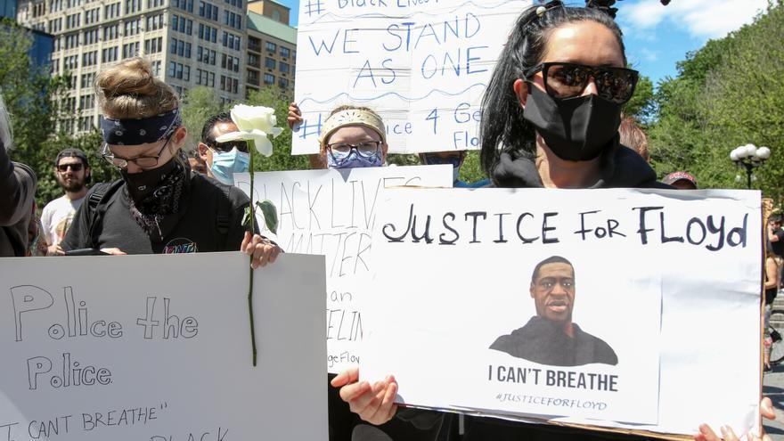 Varios manifestantes muestran carteles con las fotografías de George Floyd en protestas en EEUU.