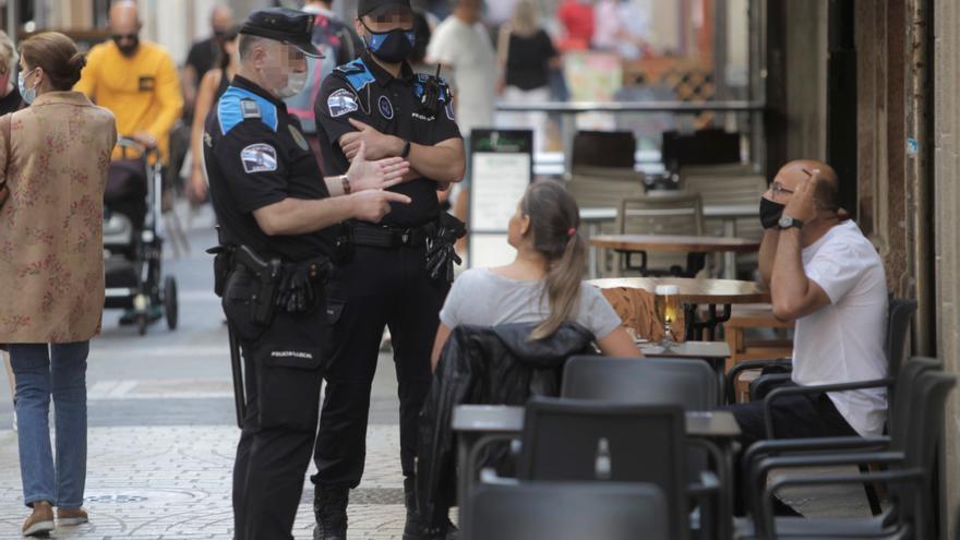 Dos agentes de la policía local de A Coruña se dirigen a un hombre que se encontraba fumando en una terraza de un bar de la ciudad. EFE/ CABALAR