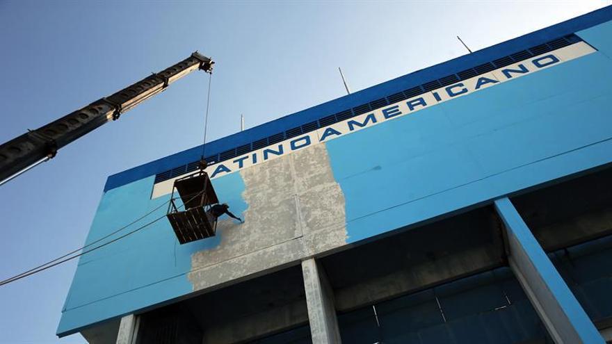 Un operario pinta el exterior de un edificio colgado de una grúa