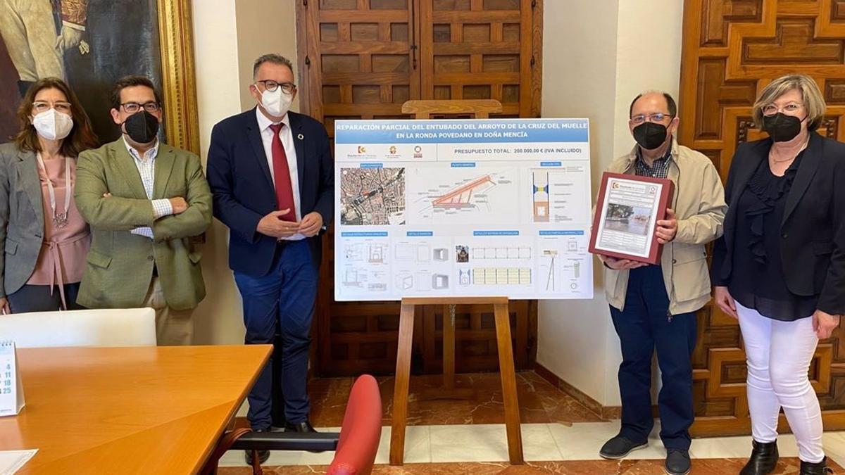 El delegado de Cohesión Territorial de la Diputación de Córdoba, Juan Díaz (tercero por la izda.), entrega al alcalde de Doña Mencíael proyecto de reparación el arroyo de la Cruz del Muelle.