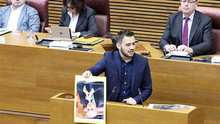 El portavoz de Compromís, Fran Ferri, sostiene cara abajo una foto del exconseller popular Rafael Blasco, condenado por corrupción