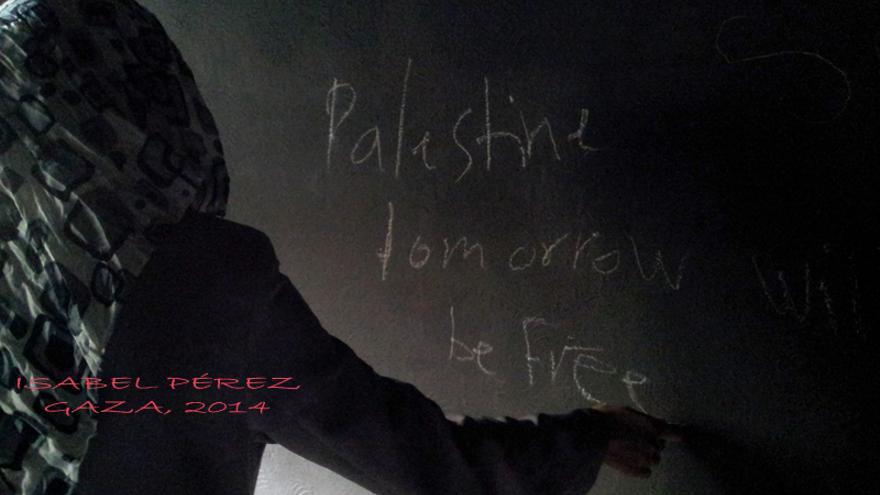 """Joven palestina escribe en la pared de su dormitorio carbonizado: """"Palestina mañana será libre"""". Foto: Isabel Pérez, Khuza'a, 5 de agosto de 2014."""