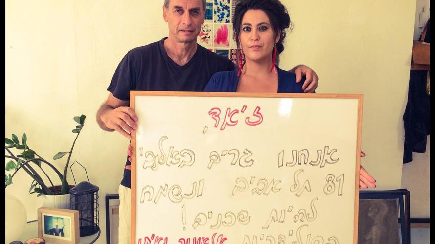 Eléonore y Eitan Bronstein, directores de De-Colonizer, con un cartel dando la bienvenida a un nuevo vecino palestino en el inmueble donde viven en Tel Aviv. | Foto cedida por De-Colonizer.