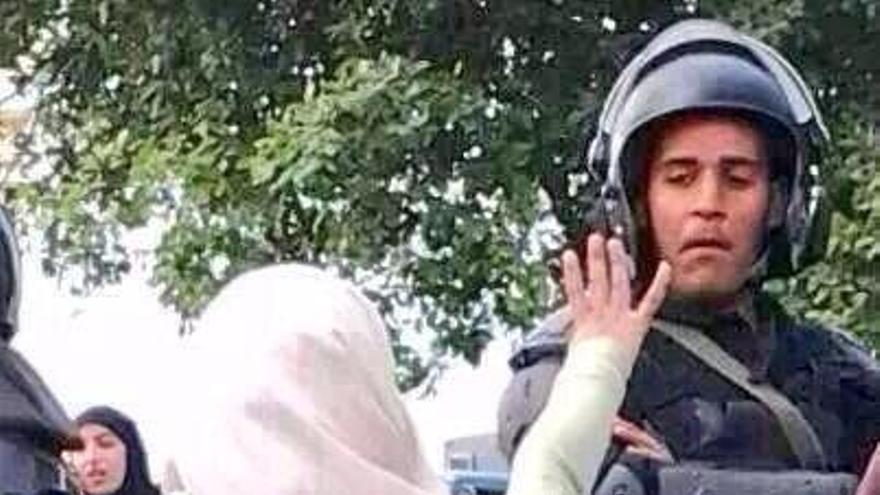 Mujer egipcia hace el signo de la Hermandad Musulmana frente a un policía. Fuente: Abrara Rageh en Twitter