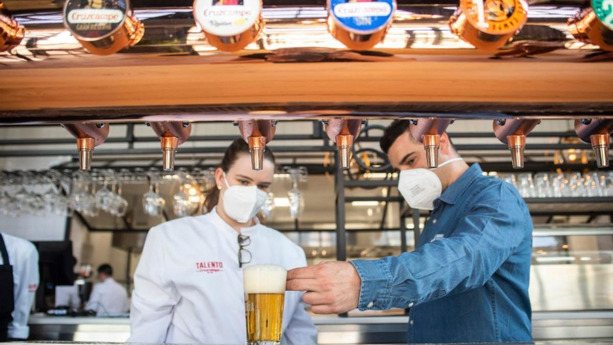 Dos camareros sirviendo una cerveza en su establecimiento