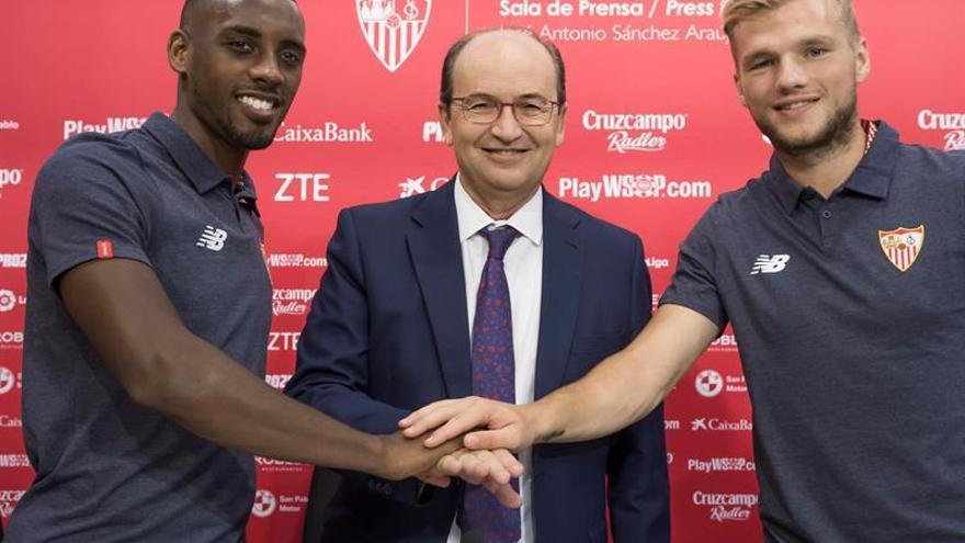 El presidente del Sevilla FC, José Castro(c) posa con los jugadores, el lateral izquierdo Lionel Carole (i) y el centrocampista, Johannes Geis(d)