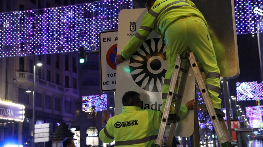 Dos operarios colocan una de las señales que indican los accesos a Madrid Central