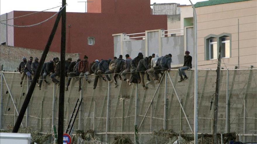 Un grupo de personas permanece encaramada a la valla en una imagen de archivo / EFE