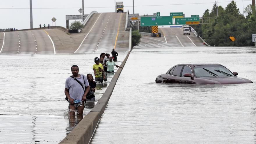 Evacuados por los efectos de la tormenta Harvey recorren una inundada Interestatal 610