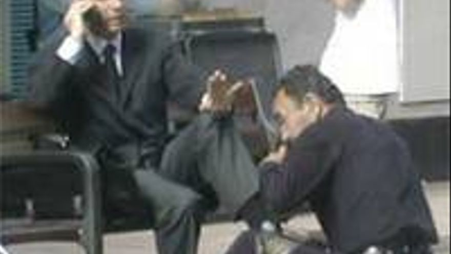 Jorge Rodríguez, arreglando un apaño mientras le limpian los zapatos en Triana.