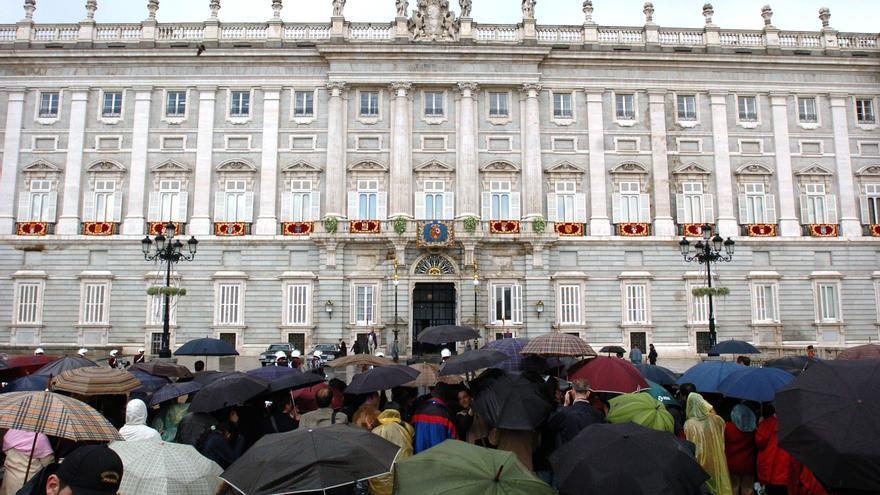 MADRID, 22-05-2004.- Numerosas personas se congregan, a pesar de la lluvia, frente a uno de los balcones del Palacio Real, donde harán su aparición los recién casados Príncipes de Asturias, para felicitarles por su enlace, celebrado hoy en la Catedral de la Almundena de Madrid. EFE/EMILIO NARANJO