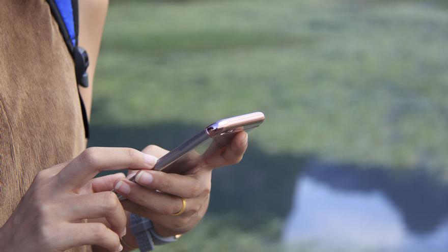 Una persona usa un teléfono móvil.