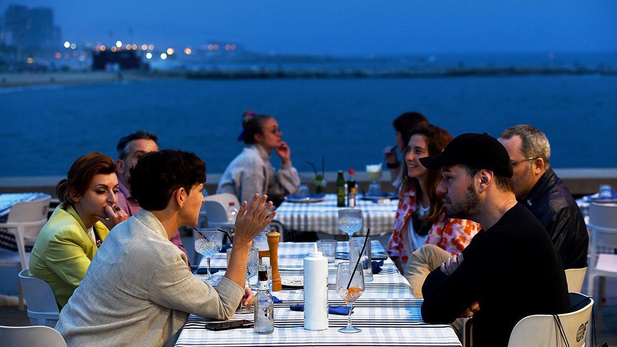Un grupo de amigos cena frente al mar en el Port Olímpic de Barcelona