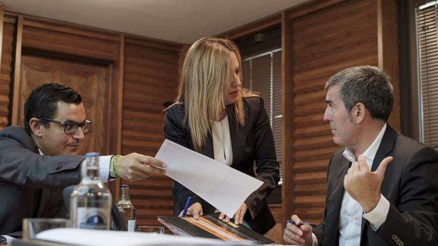 El presidente del ejecutivo regional, Fernando Clavijo (d); el consejero de Obras Públicas y Transportes, Pedro Rodríguez (i), y la consejera de Hacienda, Rosa Dávila, charlan momentos antes de una reunión del Consejo de Gobierno