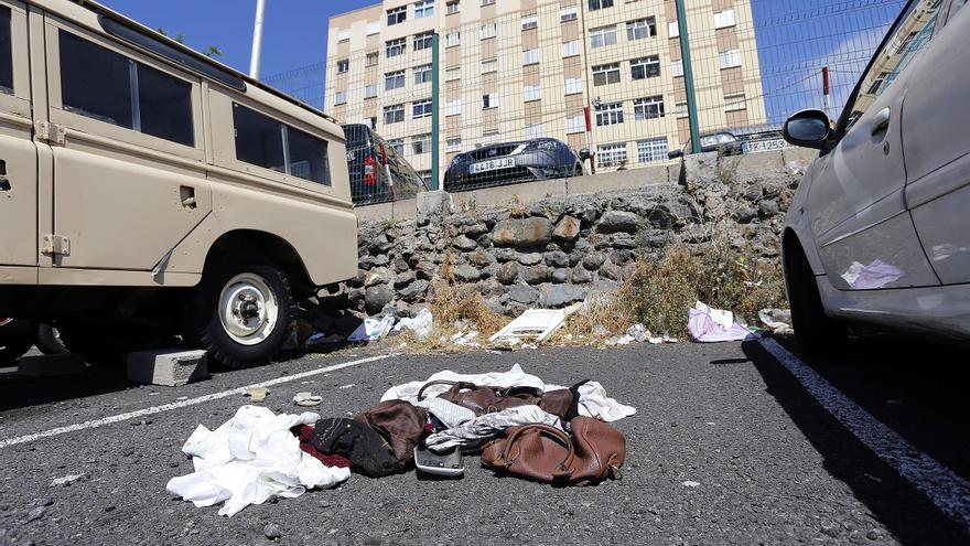 Restos de ropas dejados en el asfalto de una plaza de aparcamiento