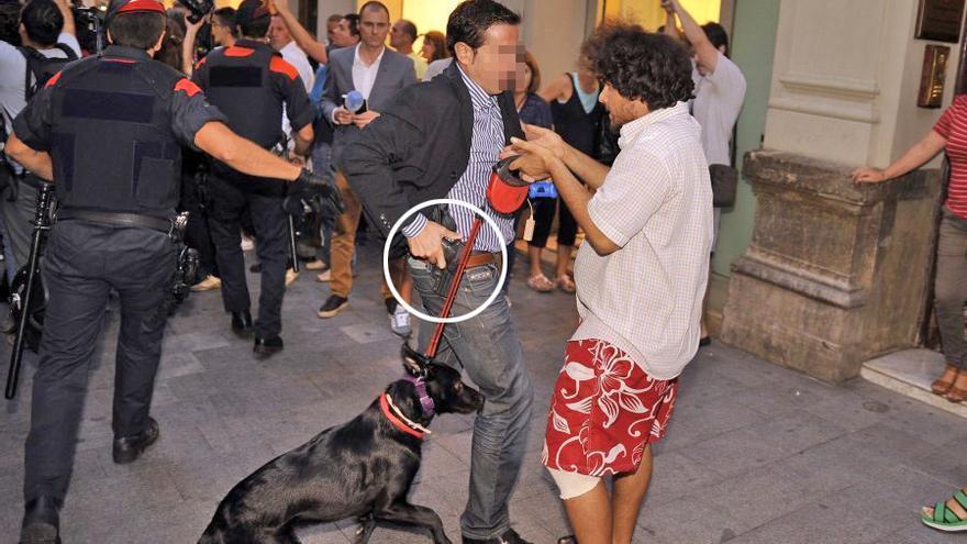 Un agente muestra la pistola a un manifestante durante una protesta en un acto de Rajoy. Foto: Alfredo González (El Diari de Tarragona)