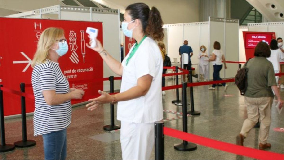 Una enfermera toma la temperatura a una ciudadana en el punto de vacunación contra el coronavirus en València.