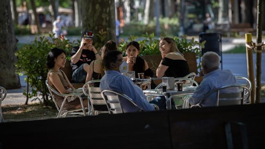Varias personas disfrutan en la terraza de un bar de Barcelona durante el segundo día de la reapertura al público de las terrazas al aire libre de los establecimientos de hostelería y restauración limitándose al 50% de las mesas