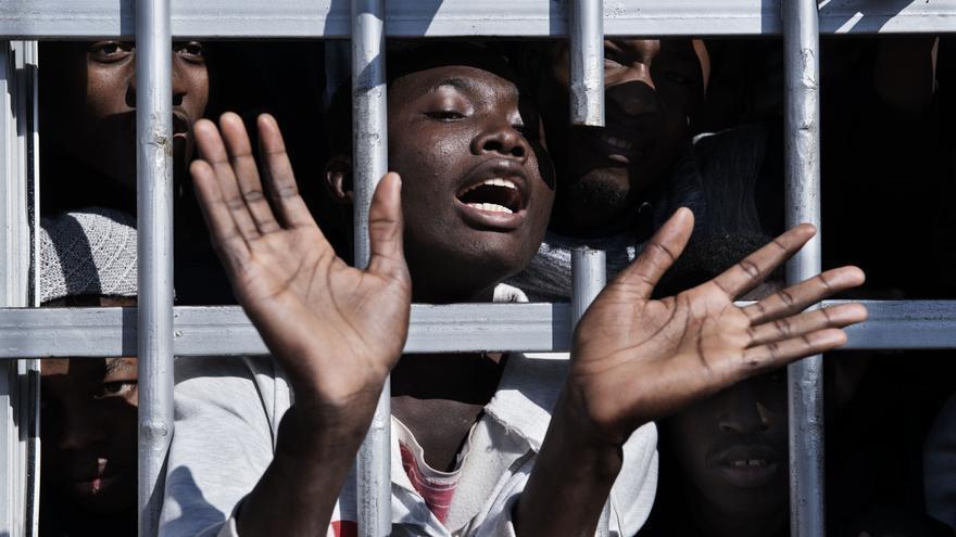 Un migrante gesticula desde detrás de las barras de una celda en un centro de detención en Libia, en enero de 2017.