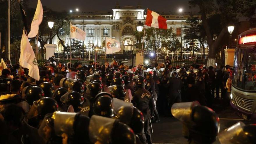 Ciudadanos celebran el anuncio del presidente de Perú, Martín Vizcarra, del cierre del Congreso este lunes, en el exterior del edificio, en Lima (Perú)