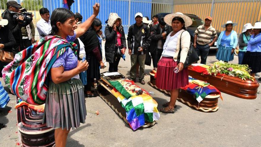 Ciudadanos rodean los féretros de varios de los fallecidos tras los disturbios de ayer con las fuerzas del orden, frente al Instituto de Investigaciones Forenses este sábado, en Cochabamba (Bolivia).