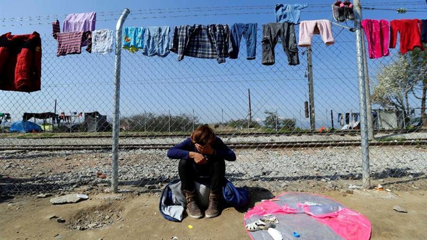 Una mujer bajo la ropa tendida en la valla que delimita Grecia con Macedonia, en el campamento de Idomeni en Grecia.
