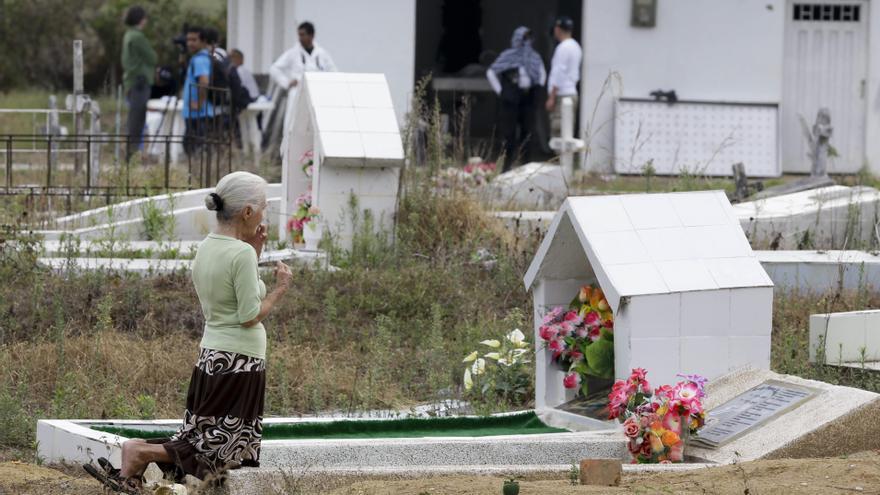 Una mujer se arrodilla junto a una tumba en el cementerio de La Macarera, en Colombia © AP Photo/Fernando Vergara