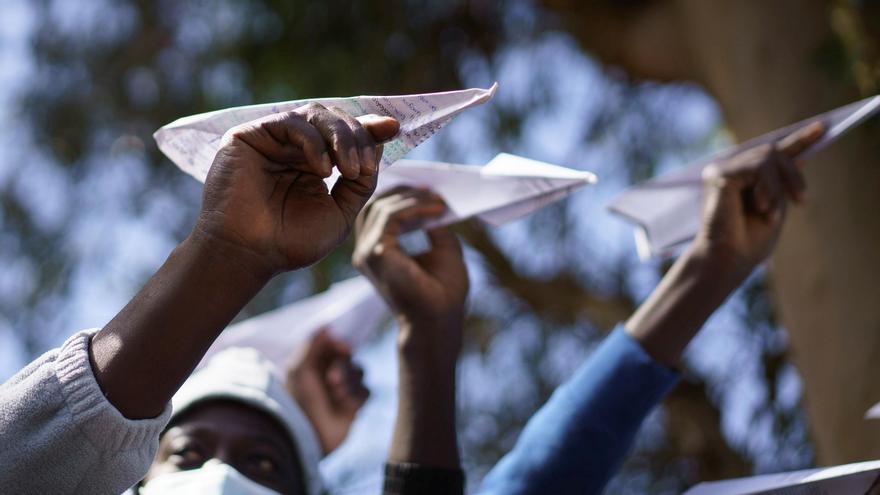 Migrantes lanzan aviones de papel en el campamento de Las Raíces para pedir que se les deje continuar con su proyecto migratorio