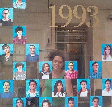 Almudena Mora, coordinadora de la exposición, posa entre los retratos de la instalación situada en la antigua Óptica Langa   Foto: A. Pérez