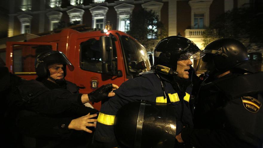 Los agentes conducen al bombero a un vehículo policial / Olmo Calvo