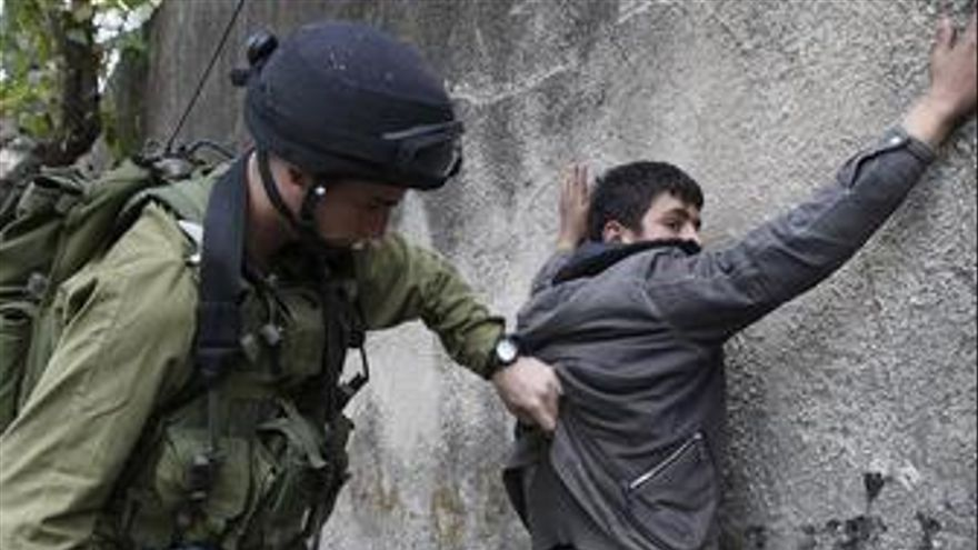 Soldado de Israel cacheando a un palestino en Gaza