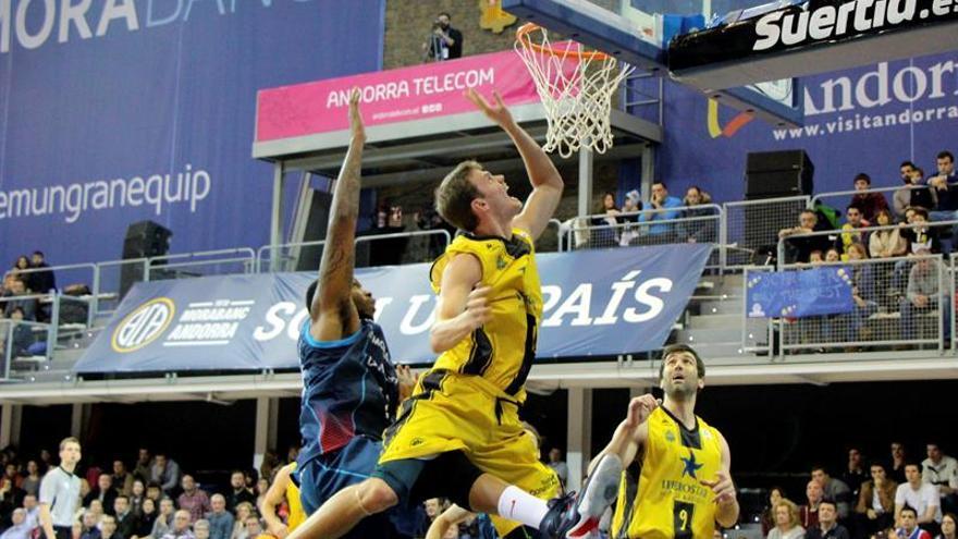El alero estadounidense del Iberostar Tenerife, Timothy James Abromaitis (c), entra a canasta ante el jugador del MoraBanc Andorra, durante el encuentro correspondiente a la jornada 20 de la liga ACB, disputado en el pabellón Poliesportiu d'Andorra. EFE ANA / Borja Nolla.