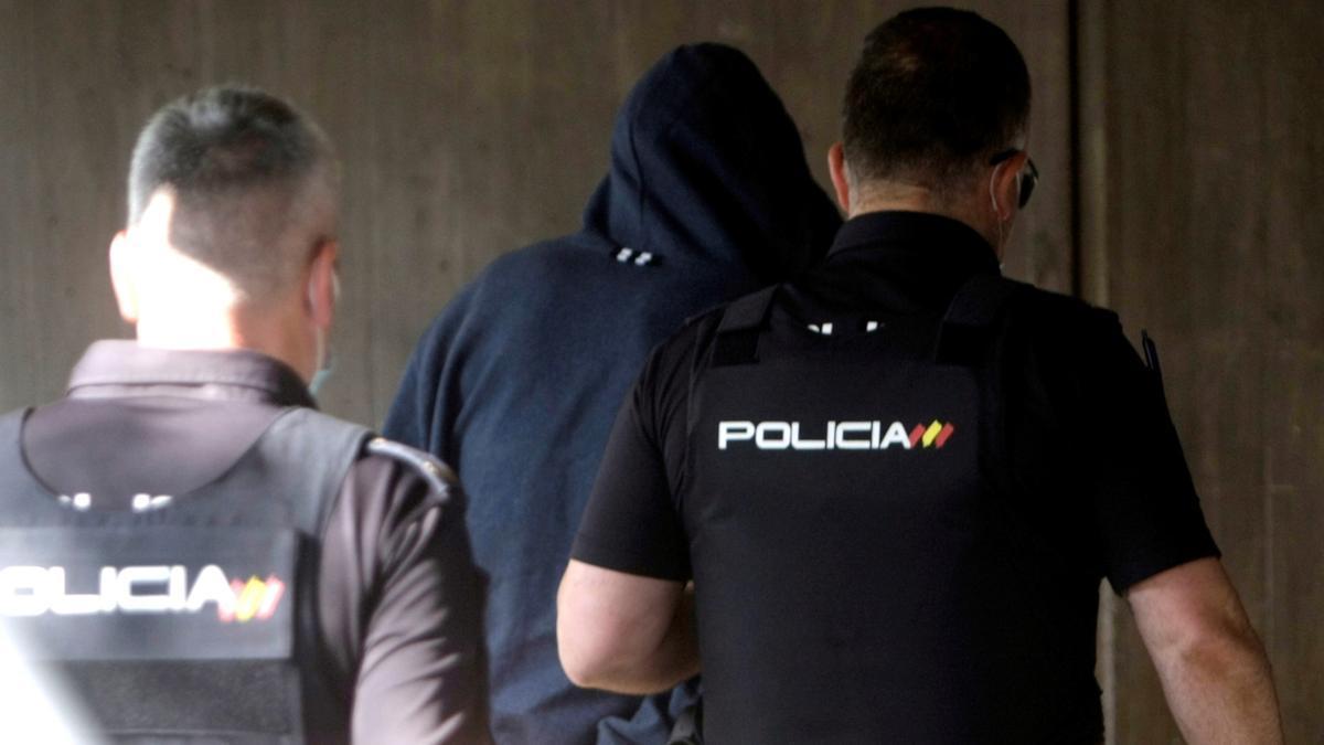 Agentes de la Policía Nacional conducen a uno de los cuatro detenidos por el homicidio de Samuel Luiz este viernes al interior de los juzgados de la Coruña.