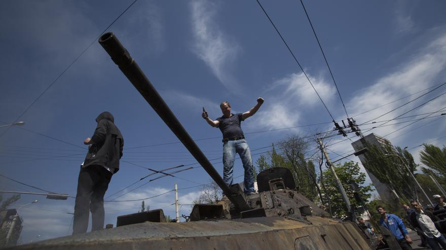 Un hombre local se encuentra encima de un carro de combate incautado que prendió fuego en el centro de Mariupol, Ucrania oriental, Sábado, 10 de mayo 2014, después de intensos combates entre las fuerzas del gobierno de Ucrania y los manifestantes pro-rusos. Copy: AP Photo/Alexander Zemlianichenko
