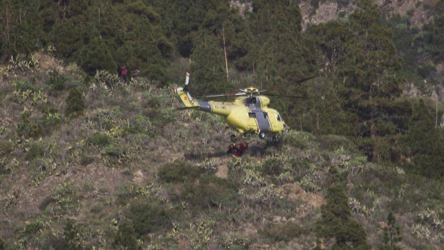 Momento en el que el helicóptero del GES recoge al accidentado tras ser trasladado en camilla por los bomberos del Parque de La Laguna hasta la zona donde podía evacuarlo la aeronave. Foto: Antonio Camacho.