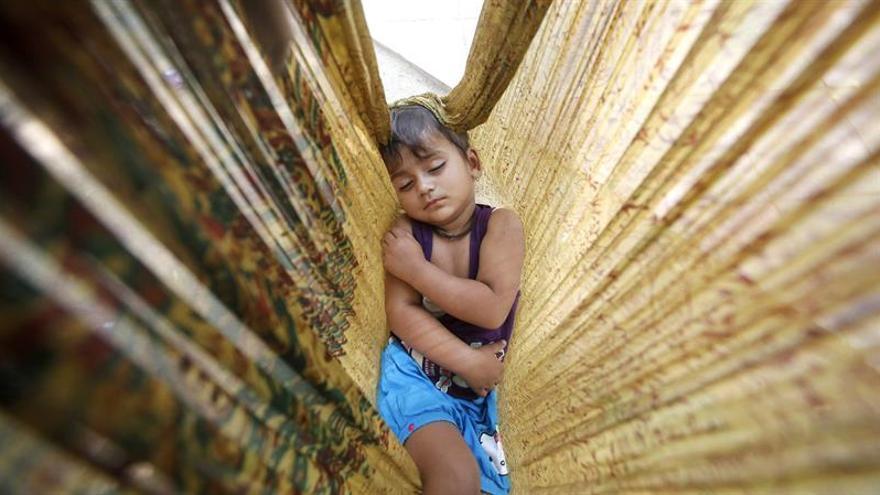 Un niño duerme en una hamaca de tela en Nueva Delhi.  