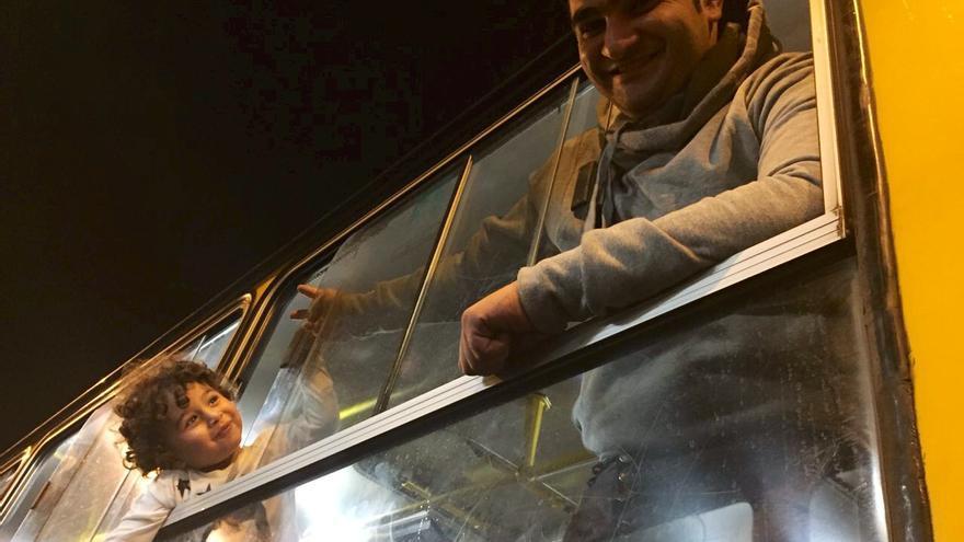 Un adulto y un niño se asoman por la ventana del autobús que les lleva hasta la frontera austriaca tras días hacinados en la estación de Keleti. / Olga Rodríguez