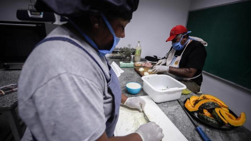 """Personas preparan comida en un comedor de los denominados de los """"curas villeros"""" el 31 de marzo de 2020 en Buenos Aires (Argentina)."""