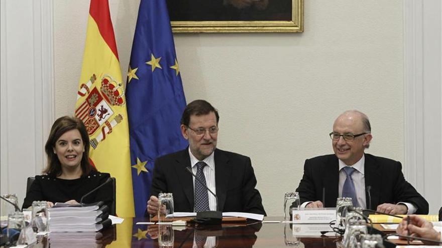 Rajoy junto a la vicepresidenta y el ministro de Hacienda