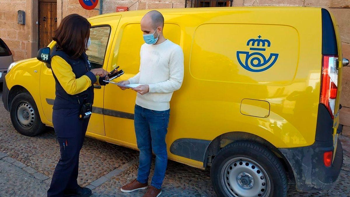 Una trabajadora de Correos con una PDA ante un usuario.