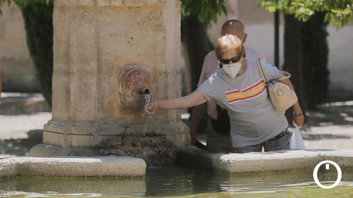 Una mujer se refresca en la fuente del Patio de los Naranjos