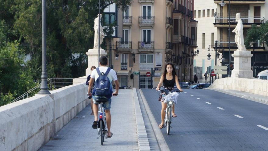 Dos ciclistas se cruzan en un puente de Valencia.