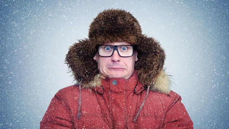 Hombre calentándose del frío con un abrigo y gorro