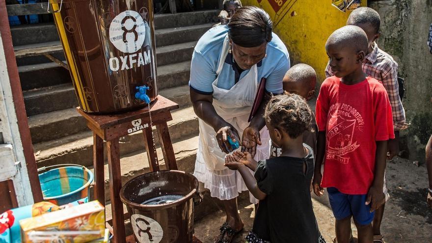 ©Tommy Trenchard / Oxfam. Una trabajadora de Oxfam  enseña a los niños a lavarse las manos en un punto de lavado de manos en una zona de Freetown, Sierra Leona.