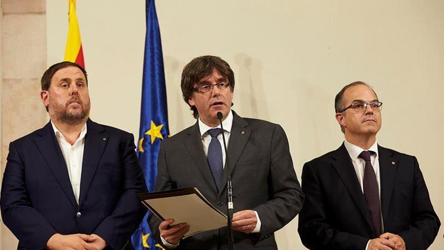 El presidente de la Generalitat, Carles Puigdemont (c), acompañado por el vicepresidente Oriol Junqueras (i) y el conseller de presidencia Jordi Turull.